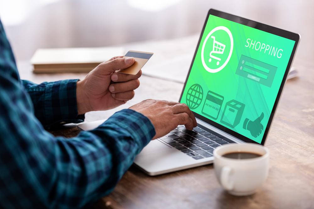 Person mit Kreditkarte in der Hand kauft in einem Online-Shop ein.